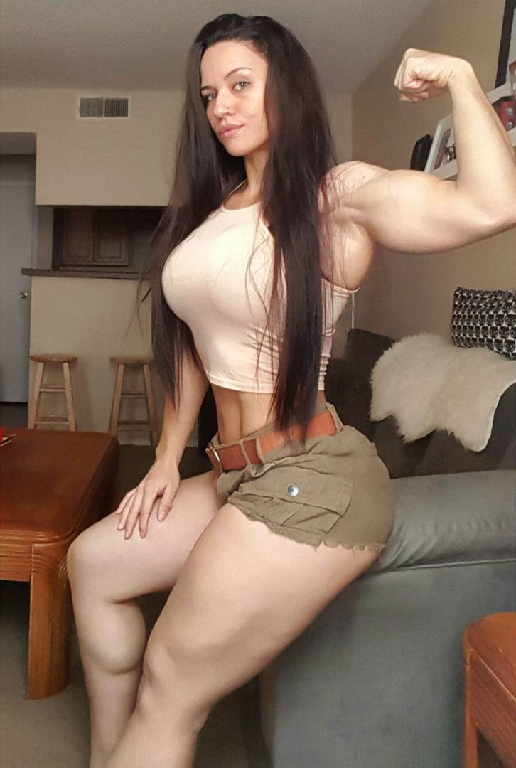 Renee Enos sitting on the sofa in shorts and t-shirt flexing her huge bicep