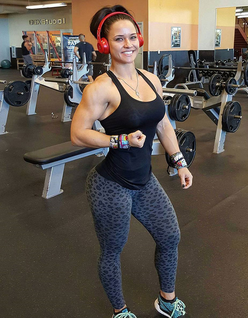 Renee Enos standing in the gym smiling looking happy flexing her right bicep just below the waist wearing her gym clothes