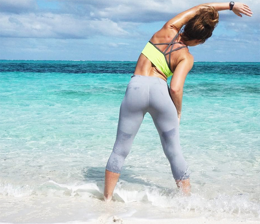 Sami Bossert stretching in the sea and sand.