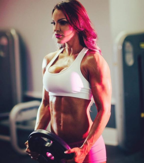 Sarah Allen doing front plate raises, as she flexes her ripped abs and arms for the photo