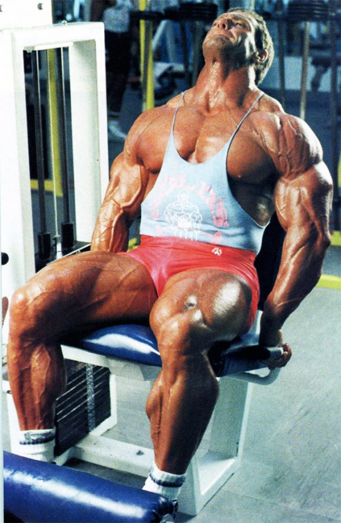 Scott Wilson Bodybuilder Stats, showing his muscular definition in his legs and upper body, while training on a leg press machine.