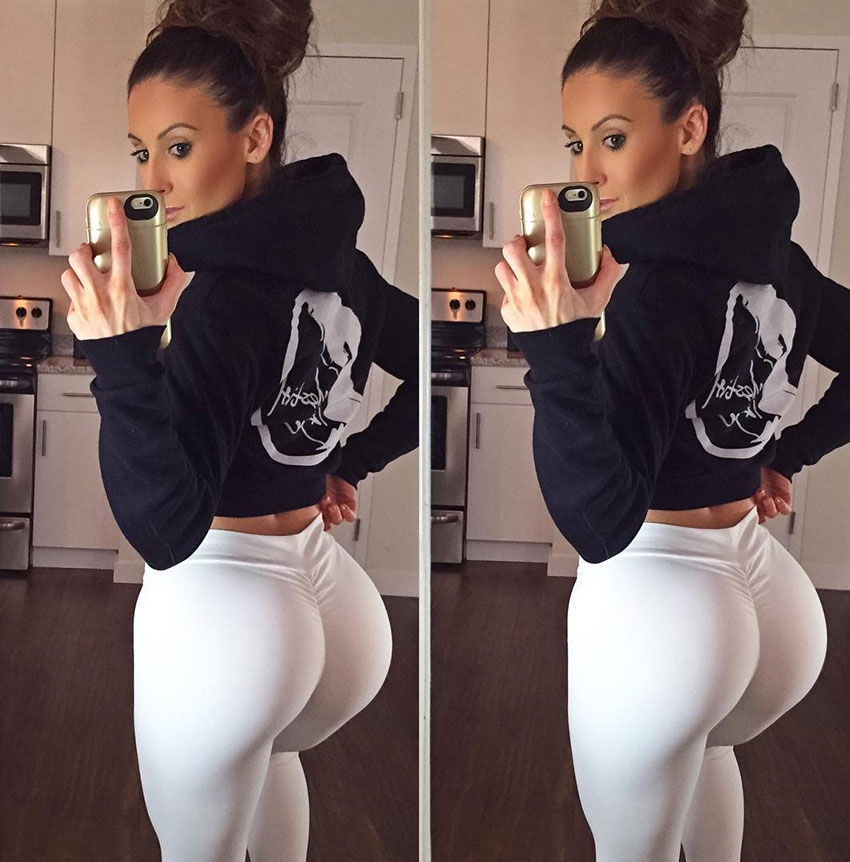Shaunna Marie wearing white trousers taking a selfi showing her large glutes