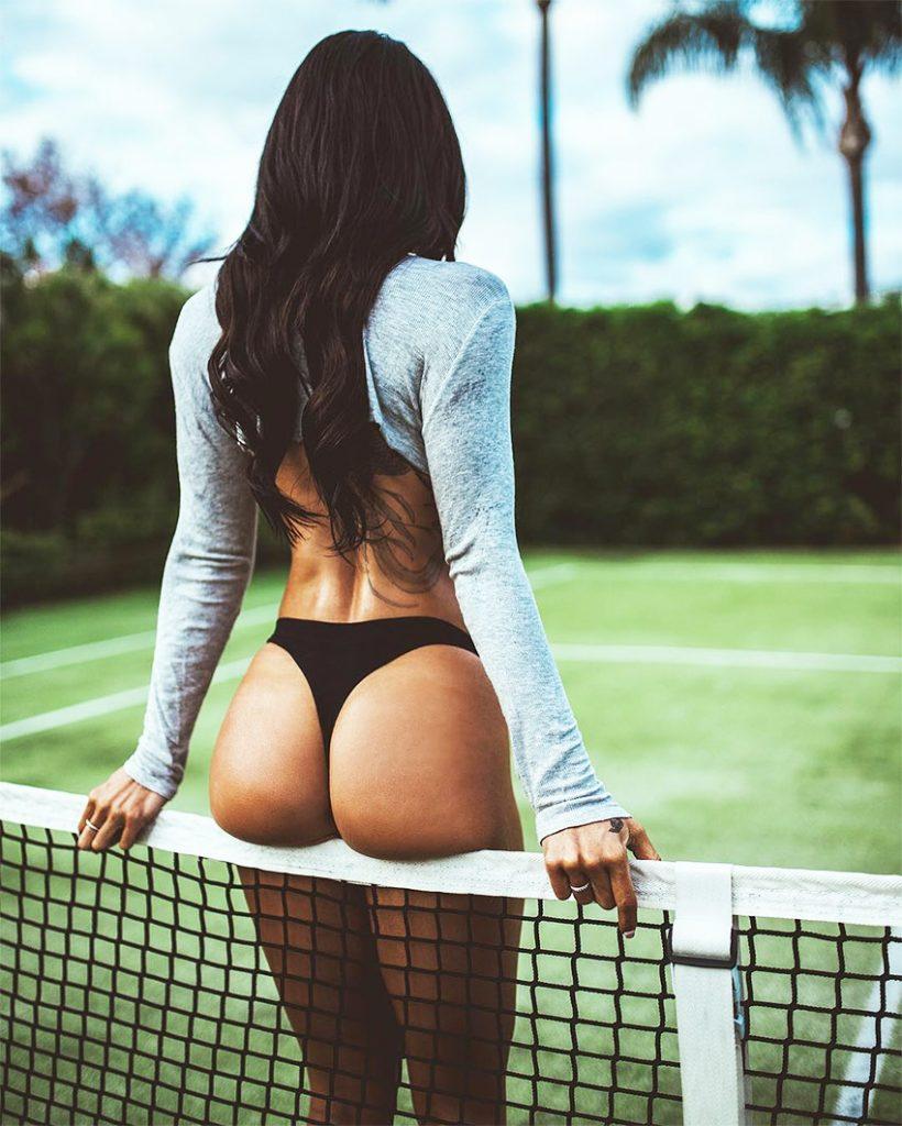 Steph Pacca prezentând ca model de fitness într-un teren de tenis într-un bikini, afișează glutele musculare și picioarele.