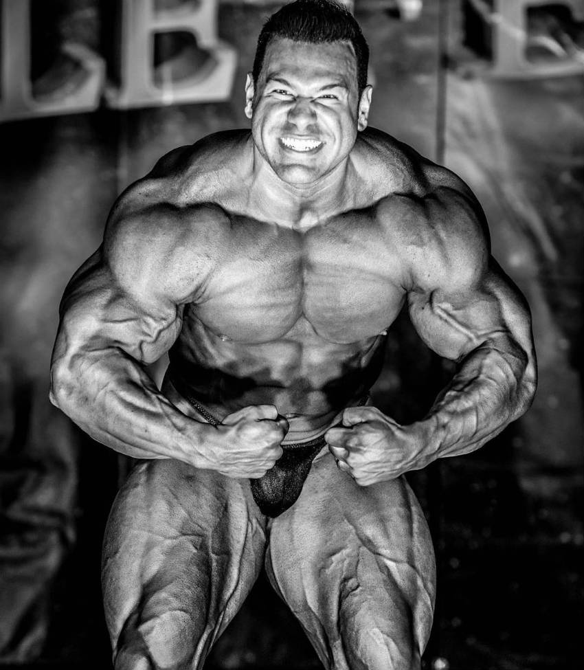 Steve Kuclo flexing at a competition (black and white)