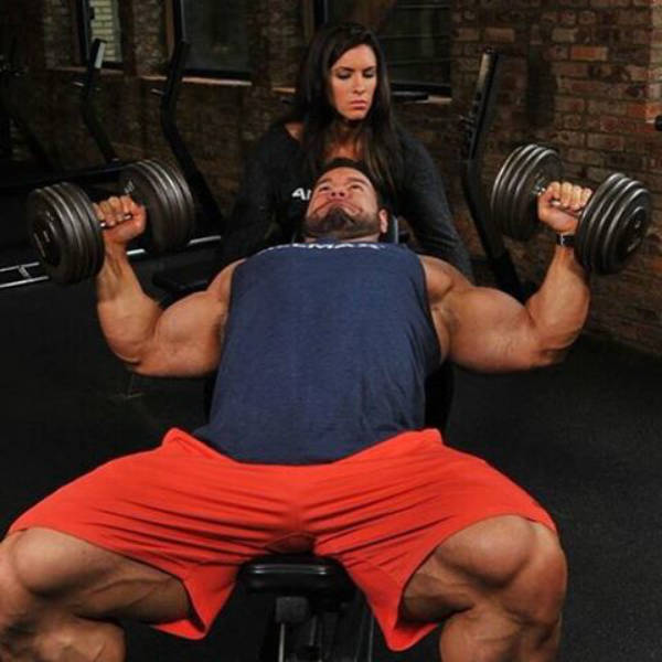 Steve Kuclo completing a chest flye with his wife spotting him