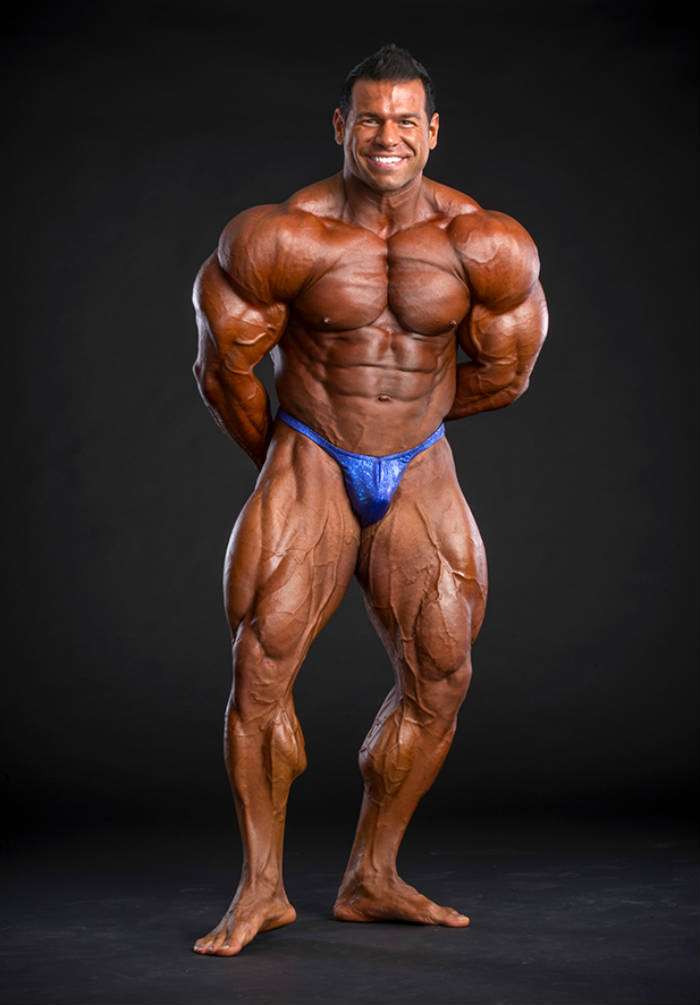 Steve Kuclo posing in full tan and blue trunks
