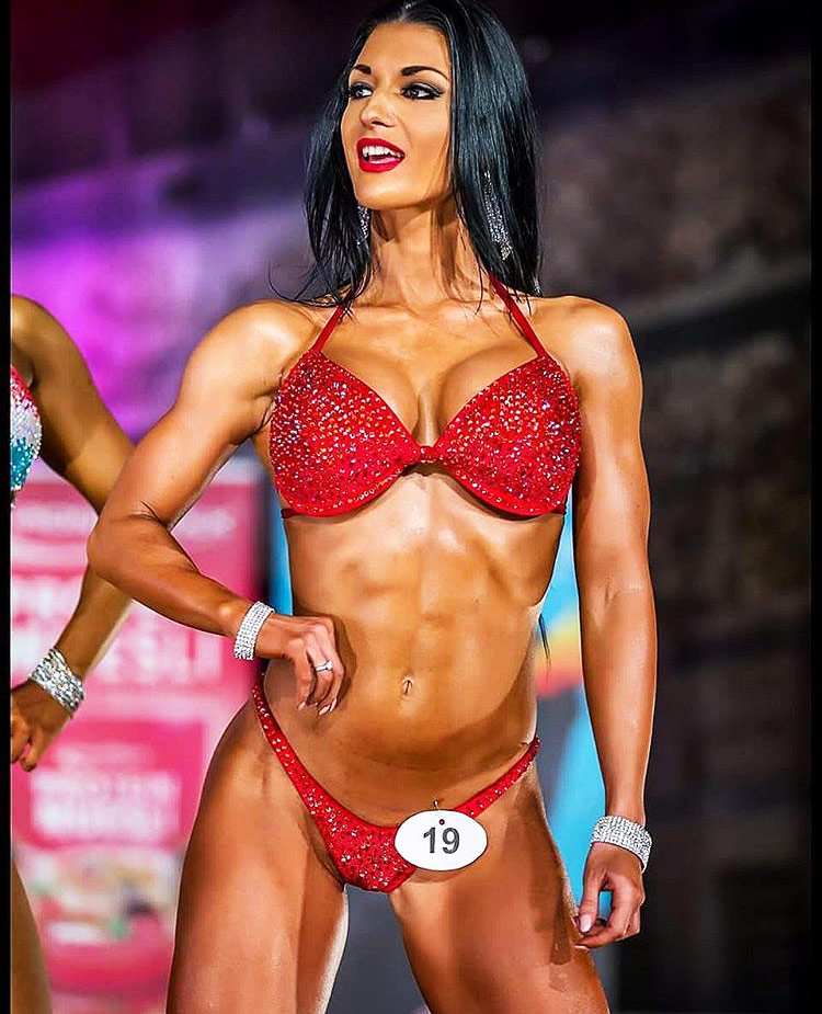 Valerija-Slapnik-posing-on-stage-as-a-bikini-athlete in a red bikini, showcasing her abs and muscular definition.