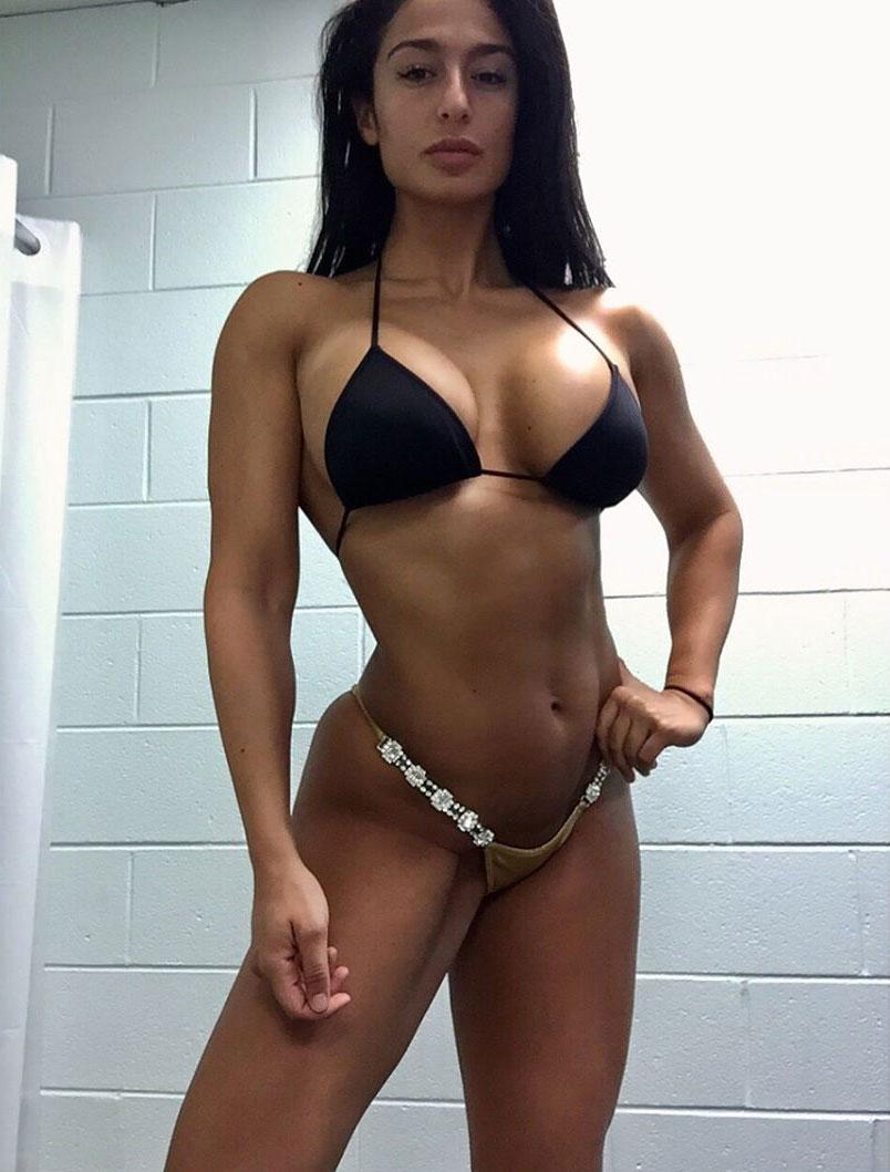 Valia Ayyar standing in a bikini flexing her muscles