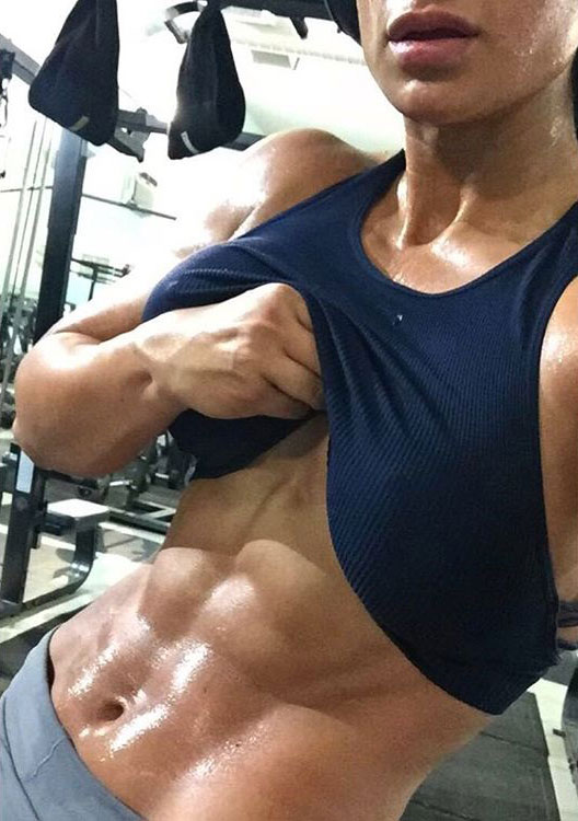 Valia Ayyar lifting up her shirt flexing her abs
