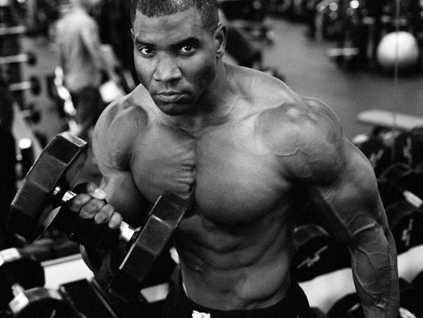 Xavisus lifting completing dumbbell curls in the gym