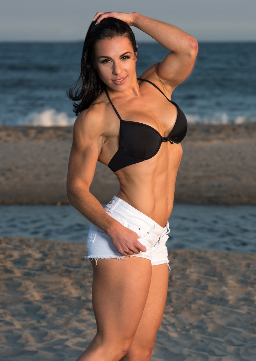 Alyssa Michelle Agostini standing on a beach, showing her ripped body in white shorts and black bra