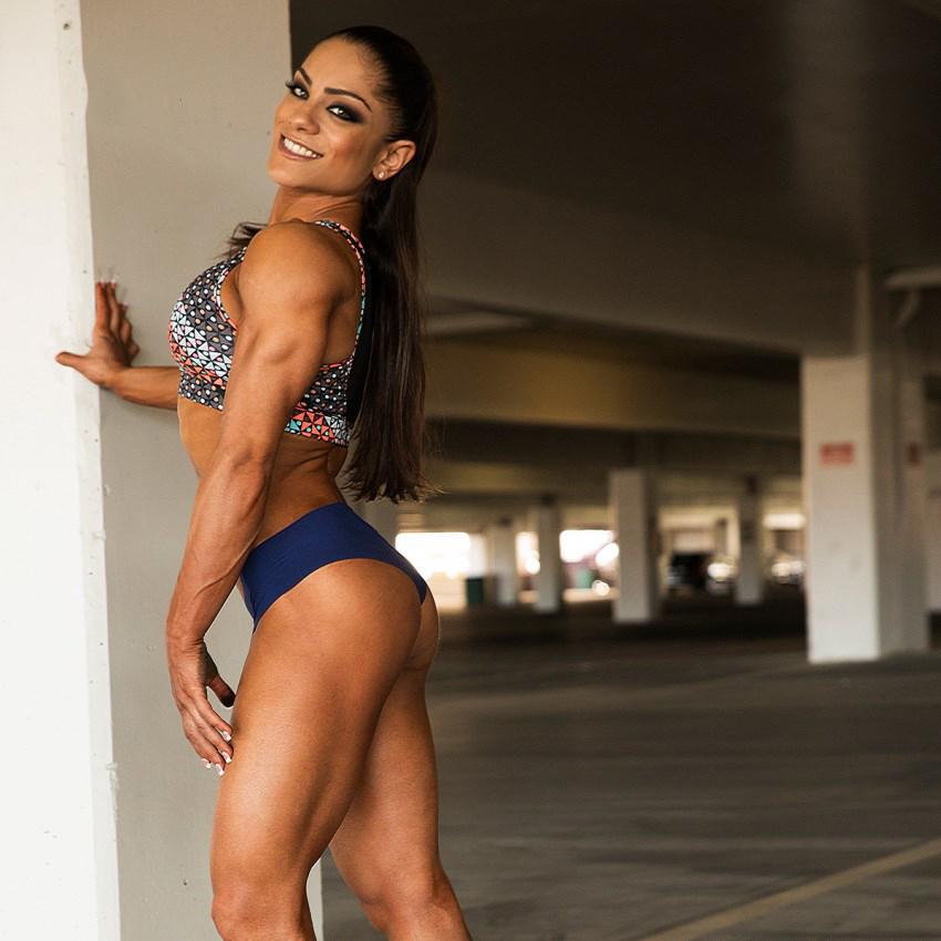 Ariel Khard leaning with her hand against the wall in a parking garage, while showing her ripped body in a bikini