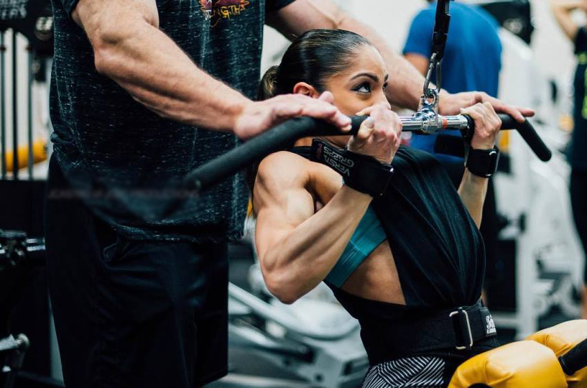 Ariel Khadr performing lat pulldowns with a man behind her who is spotting her