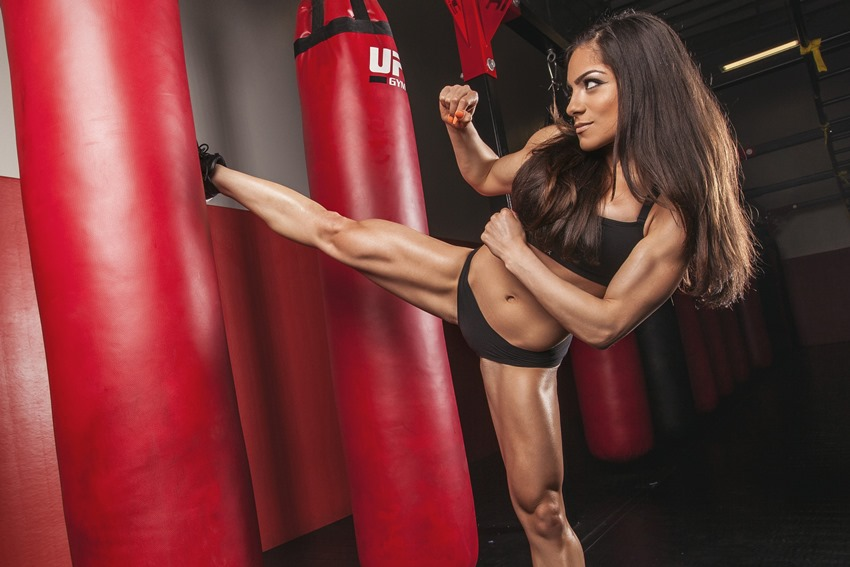 Ariel Khadr punching a boxing bag with her leg, demonstrating her awesome flexibility