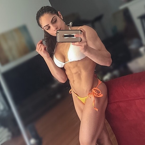 Ariel Khadr taking a selfie, displaying her perfectly sculpted body in a bikini