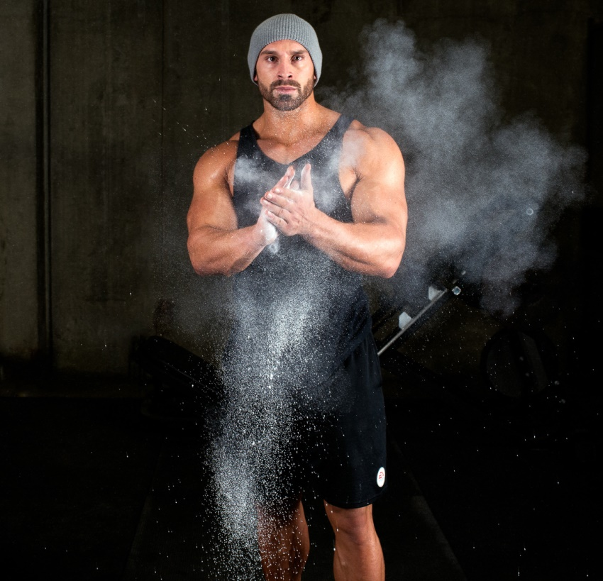 Bradley Martyn clapping his hands covered in chalk dust, spreading the dust everywhere in the air as he claps