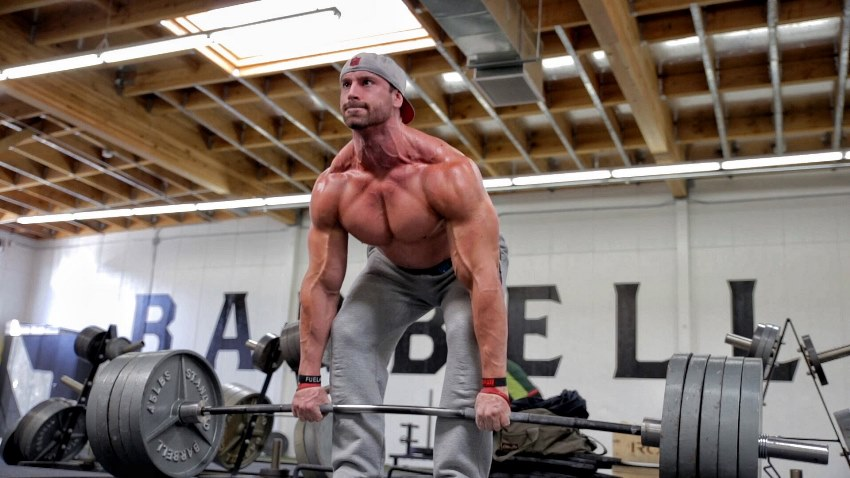 Bradley Martyn doing heavy deadlifts in the gym, with his veins popping all over his body as a result of the strenuous activity