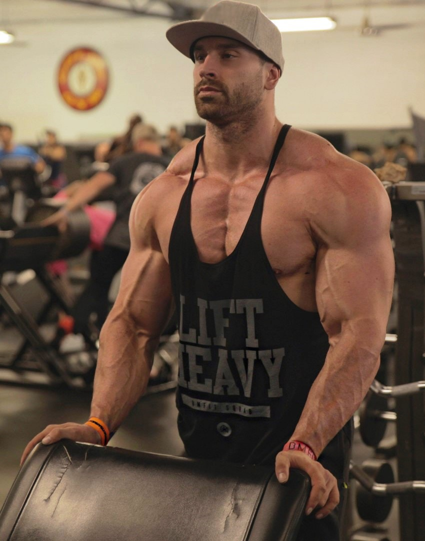 Bradley Martyn flexing his muscles while squeezing his hands against a bench