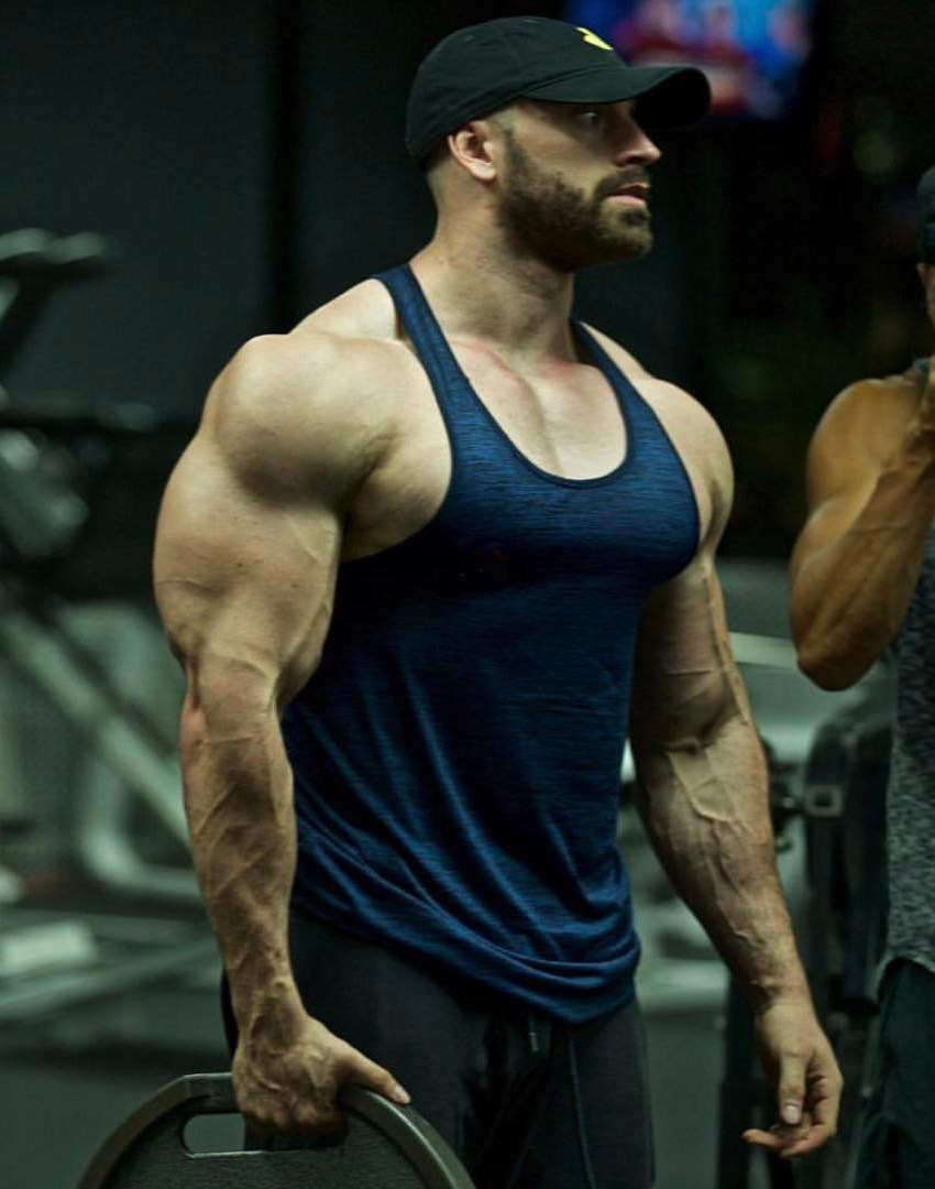 Bradley Martyn holding a weight plate with one of his super vascular and muscular arms