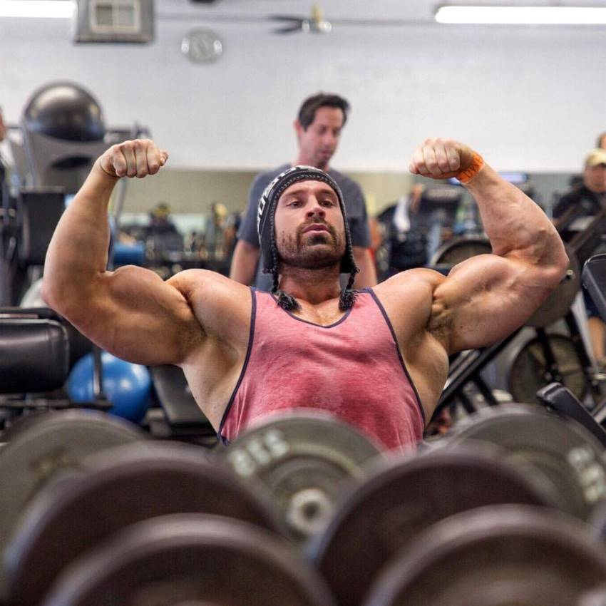 Bradley Martyn in a front double biceps pose while sitting on bench in a gym in a red tank top