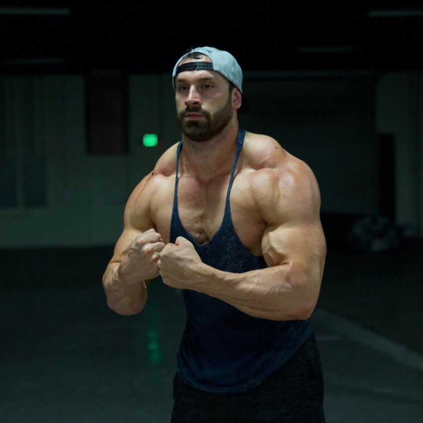 Bradley Martyn in a tank top displaying most muscular pose in the gym