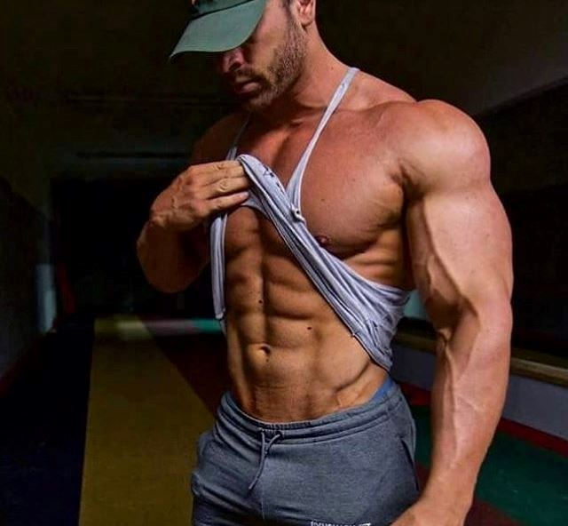 Bradley Martyn lifting his tank top to show his ripped abs