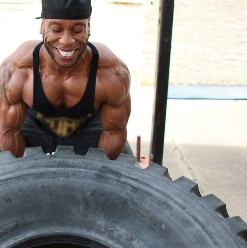 Chris Jones flipping a big tire while being in black and gold tank top, showing his incredibly ripped arms, shoulders, and pecs