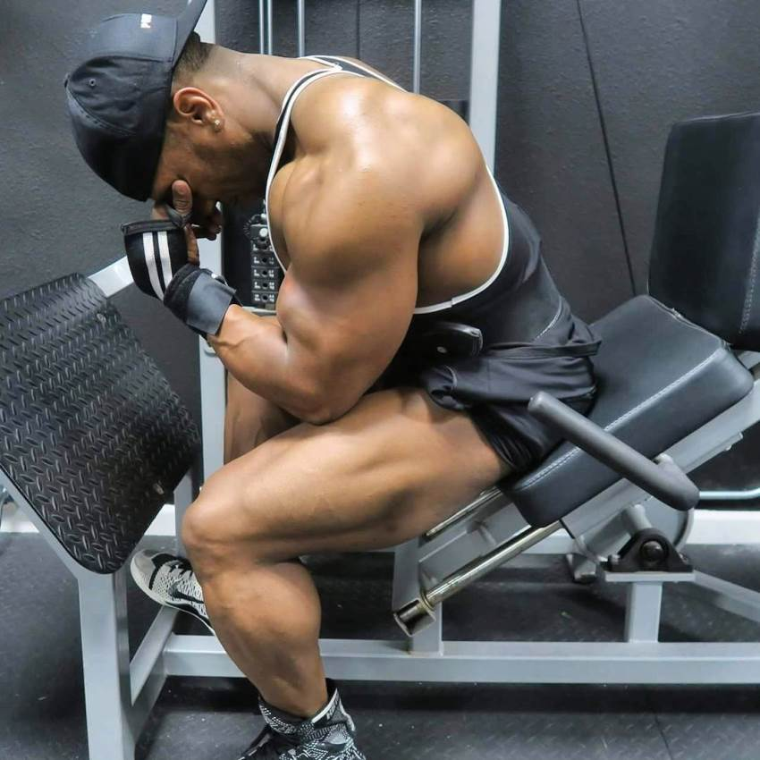 Chris Jones sitting on a leg press machine with a painful expression on his face