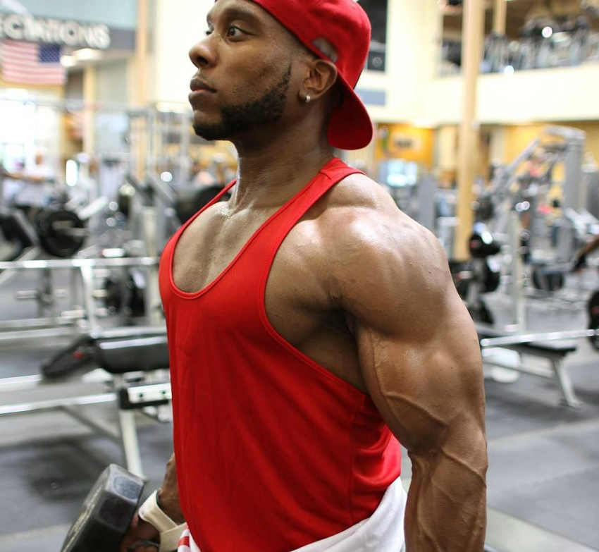 Chris Jones with dumbbells in his hands, showing his vascular and ripped arms