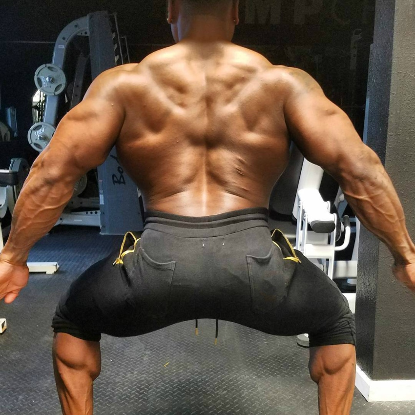 Chris Jones with his back and arms wide spread, showing his muscular lats, traps, and calves
