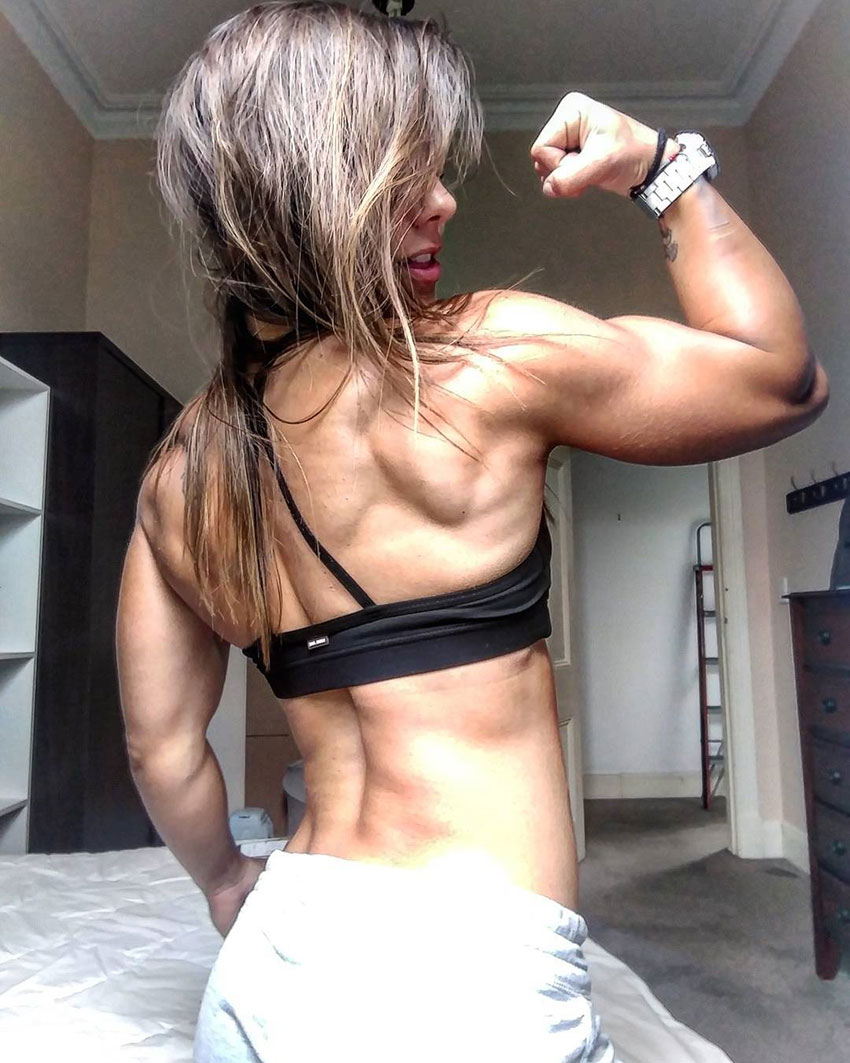 Christina Elen flexing her back and right bicep