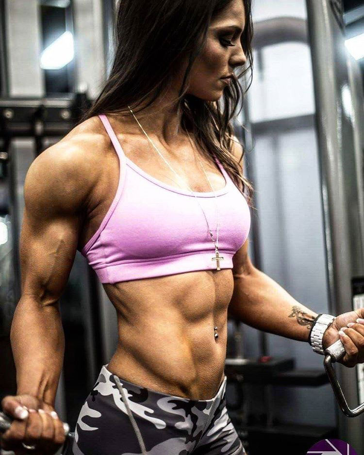 Christina Eleni performing a bicep curl in the gym looking strong and lean