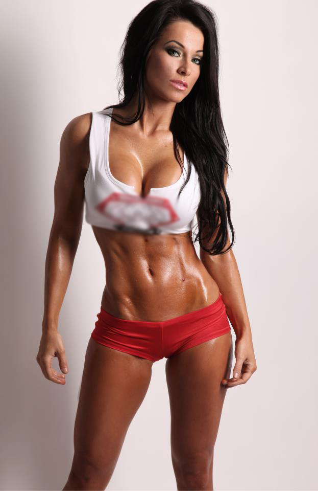 Christina Halkiopoulos posing for a photo, while showing her amazing abs, chest, arms, and legs