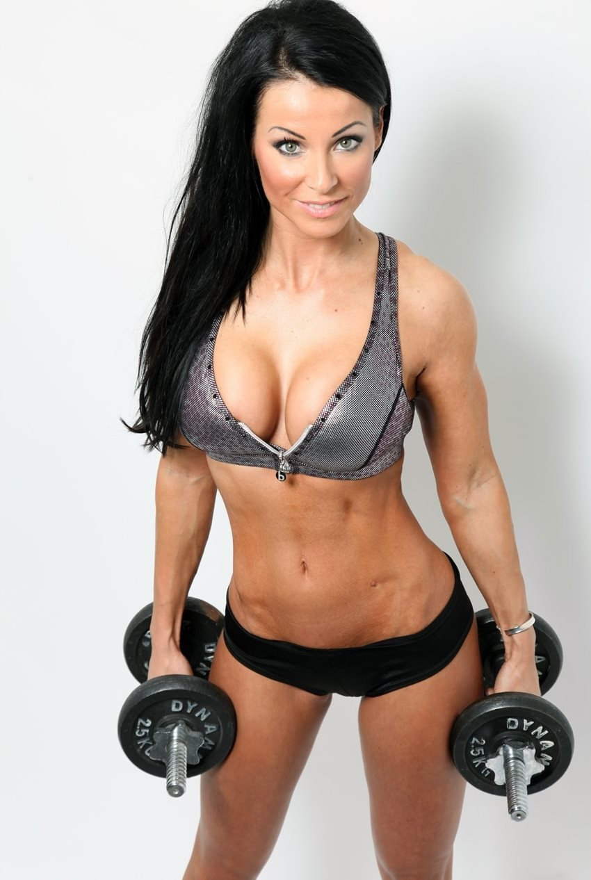 Christina Halkiopoulos profile picture, where she holds two 2,5kg dumbbells in her hands, while looking up at the camera, and showing her beach-ready body