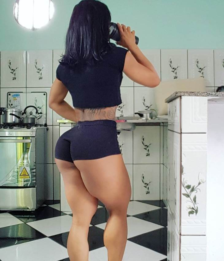 Clarice Andrade showing her amazing glutes and legs, while drinking a protein shake in a kitchen