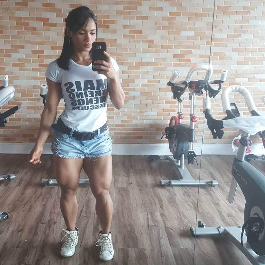 Clarice Andrade taking selfie in the gym, showing off her muscular and ripped legs from the front view