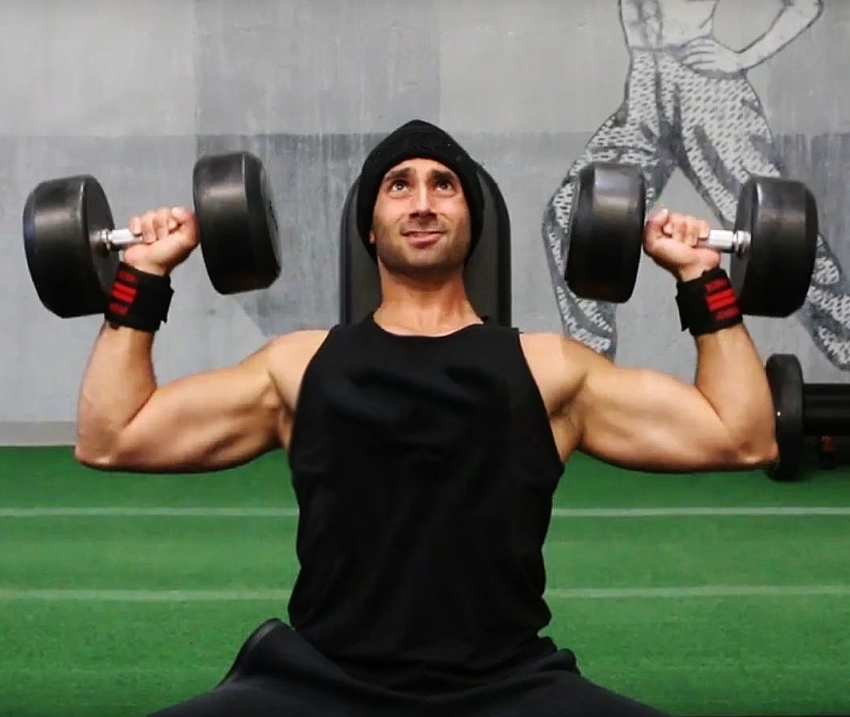 Dom Mazzetti doing a seated shoulder press on a bench