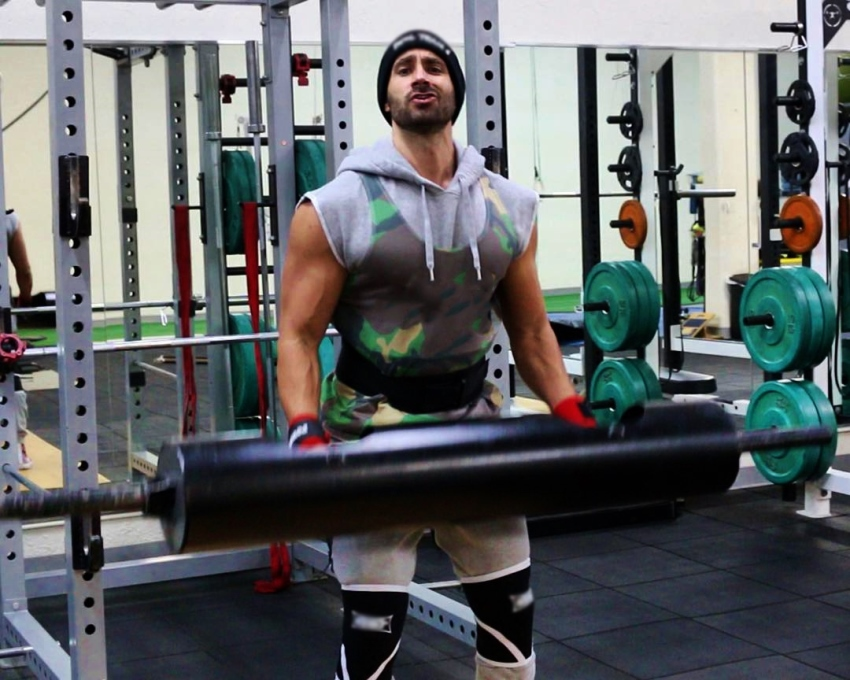 Dom Mazzetti lifting a black weight bar while saying something sarcastic into the camera