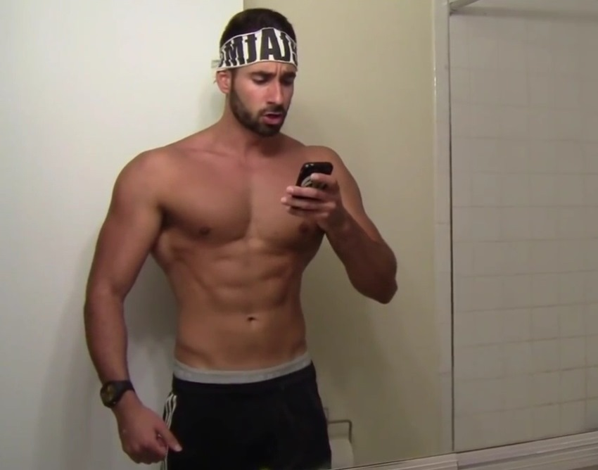 Dom Mazzetti taking a picture of himself in the mirror, showing his abs, chest, and arms