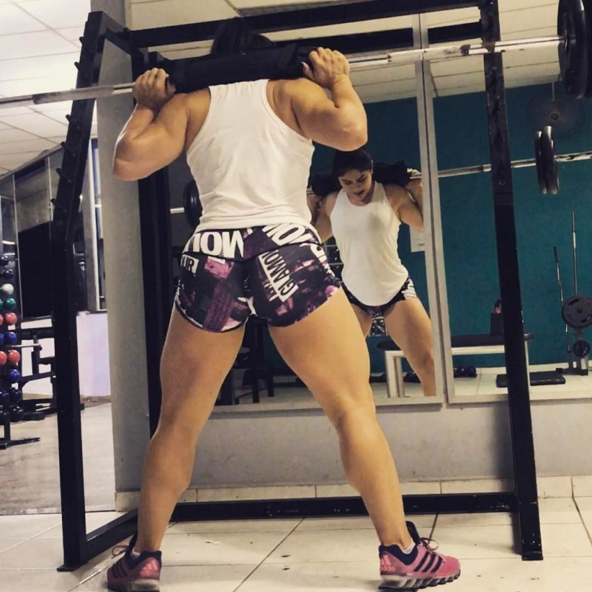 Flavia Baraky Tavares doing squats in the gym, while looking down at her feet