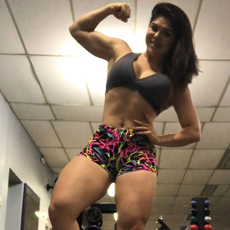 Flavia Baraky Tavares flexing her biceps while smiling at the camera