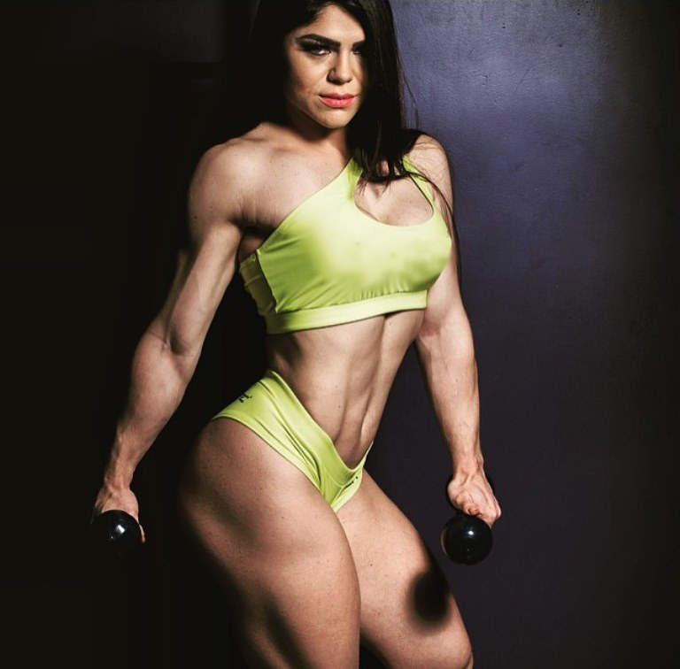Flavia Baraky Tavares' profile picture, in which she hold kettelbells in her hands, while looking straight into the camera, and showing her rippe legs, arms, and abs