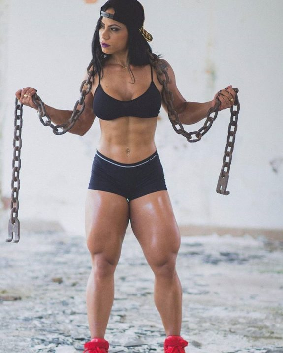 Izabelly Araujo profile picture, where she's holding chains in her arms, while looking sideways, with her body looking ripped and muscular