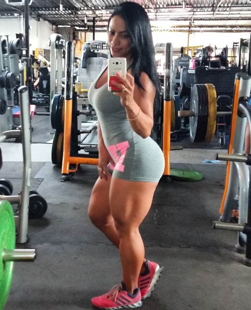 Izabelly Araujo taking another selfie in a gym, while showing her curvy legs and glutes