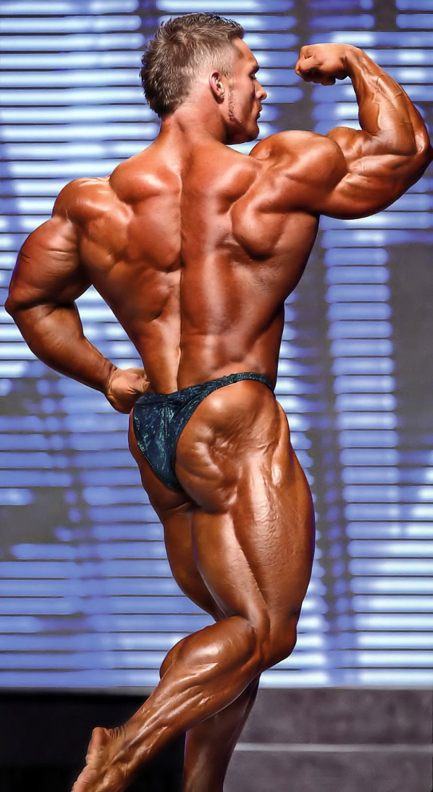 James Flex Lewis on a stage, flexing his back, glutes, and biceps