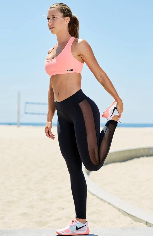 Jessie Delgado profile picture, where she stretches her quadriceps, standing near the beach