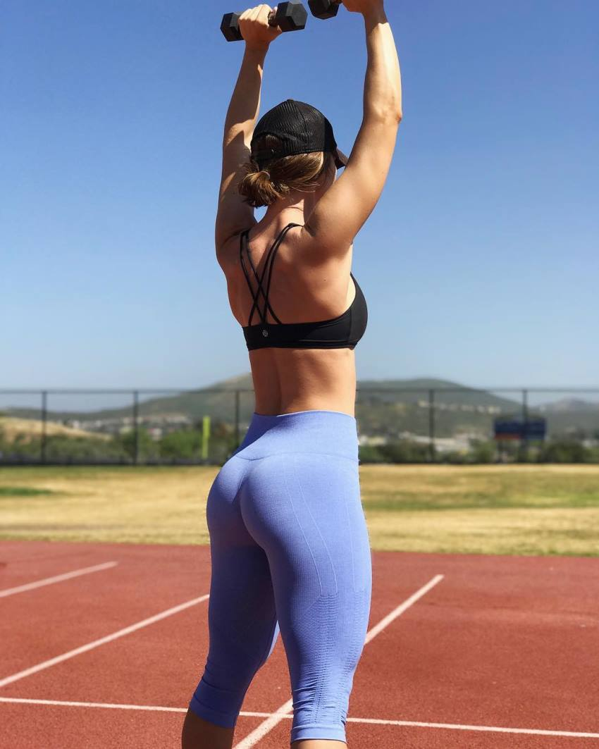Jessie Delgado showing her glutes in yoga pants while doing standing dumbbell shoulder press