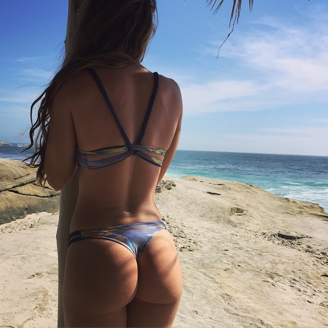 Jessie Delgado with her back turned, showing her glutes on the beach