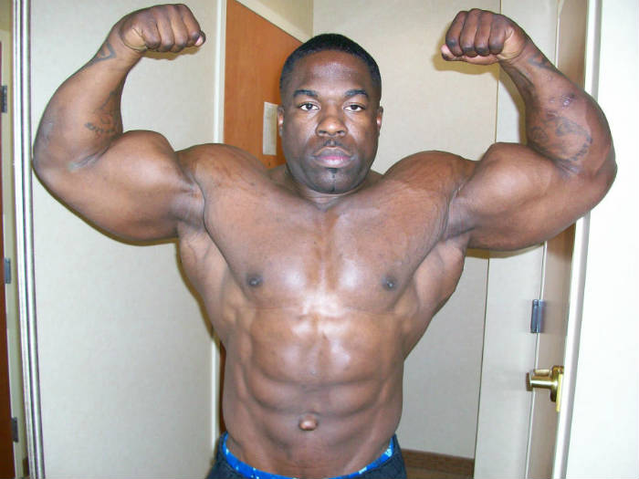 kali muscle tensing his biceps with arms over his head