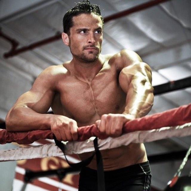 Layne Norton in a boxing ring looking in a distance while showing his sculpted chest and arms